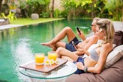 Paar die hun mobiele telefoons met behulp van door de pool royalty-vrije stock foto