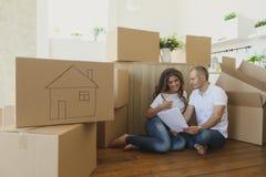 Paar die hun nieuwe keuken plannen die op de vloer situeren jonge familie die zich aan een nieuwe flat en dragende dozen bewegen stock afbeelding