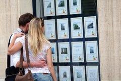 Paar die immobiliënadvertenties in de straat bekijken royalty-vrije stock foto