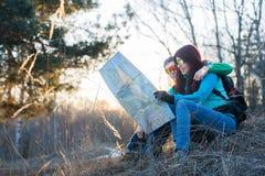 Paar die kaart bekijken terwijl het zitten op gras Stock Afbeeldingen