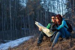Paar die kaart bekijken terwijl het zitten op gras Royalty-vrije Stock Afbeeldingen
