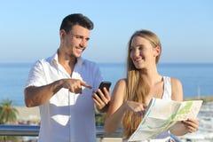 Paar die kaart of smartphonegps op vakanties bespreken Stock Foto's