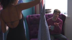 Paar die kleding selecteren bij kledingsopslag stock footage