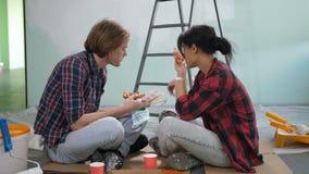 Paar die kleur kiezen van palet, die pizza eten stock videobeelden