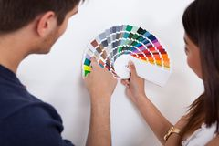Paar die kleur voor muur kiezen bij nieuw huis Stock Fotografie