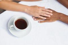 Paar die koffie hebben die samen handen houden Royalty-vrije Stock Fotografie