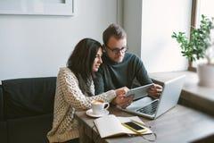 Paar die in koffie met tablet, laptop, smartphone, blocnote werken Royalty-vrije Stock Afbeeldingen