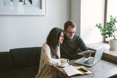 Paar die in koffie met tablet, laptop, smartphone, blocnote werken Royalty-vrije Stock Foto