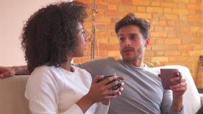 Paar die koffie op bank in woonkamer hebben stock videobeelden