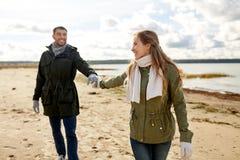 Paar die langs de herfststrand lopen stock foto's