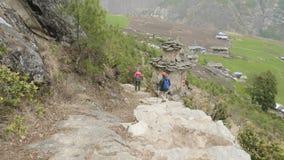Paar die langs de treden op trek rond Manaslu, dorp Prok, Nepal lopen stock videobeelden