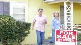 Paar die langs het Teken van de Verkoop buiten Huis betekenen stock videobeelden