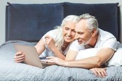 Paar die laptop met behulp van die op het bed liggen royalty-vrije stock foto