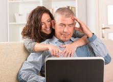 Paar die laptop thuis met behulp van stock foto's