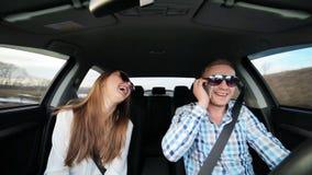 Paar die in liefde in auto het drijven het dansen, de kerel spreekt op de telefoon stock video
