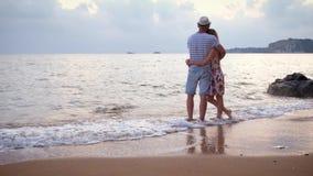 Paar die in liefde elkaar koesteren die zich op een strand bij zonsondergang bevinden stock video