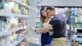 Paar die in liefde met kar in een supermarkt winkelen stock footage