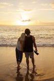 Paar die in liefde op een zonsondergang samen letten bij het strand royalty-vrije stock foto's