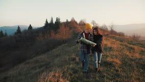 Paar die in liefde in openlucht wandelen Van de wandelaarsman en vrouw trekking die met rugzakken in sleep met binnen kaart bij z stock video