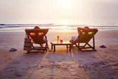 Paar die met cocktails op het strand ontspannen stock foto