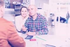 Paar die met een adviseur een aankoop bespreken stock fotografie