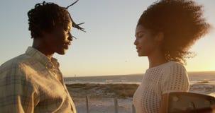 Paar die met elkaar dichtbij pick-up bij strand 4k spreken stock footage