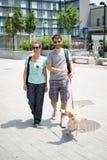 Paar die met hond in de straat lopen Stock Foto's