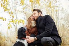 Paar die met hond in het Park en het koesteren lopen De herfstgang binnen stock foto