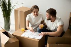 Paar die met huis binnenlands ontwerp met huisplan samen akkoord gaan stock fotografie