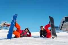 Paar die met hun snowboards in sneeuw op skihelling liggen royalty-vrije stock foto's