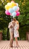 Paar die met kleurrijke ballons in het park kussen stock foto's
