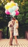 Paar die met kleurrijke ballons in het park kussen Stock Foto