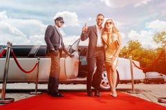 Paar die met limousine aankomen die rood tapijt lopen royalty-vrije stock afbeelding