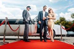 Paar die met limousine aankomen die rood tapijt lopen royalty-vrije stock fotografie
