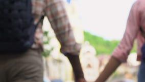Paar die met rugzakken reizen die op straat lopen, die handen, achtergrond houden stock footage