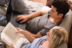 Paar die met verschillende hobbys in bed zitten royalty-vrije stock fotografie