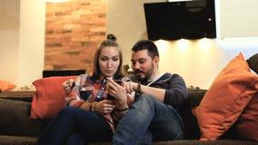 Paar die mobiele telefoon met behulp van die en pret glimlachen hebben stock videobeelden