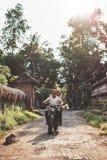 Paar die motorfiets van rit genieten door een dorpsweg Royalty-vrije Stock Foto