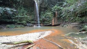 Paar die in multicolored natuurlijke pool met toneelwaterval in het regenwoud van Lambir-Heuvels Nationaal Park zwemmen, Borneo stock videobeelden
