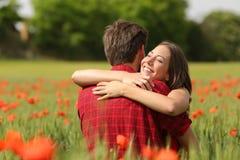 Paar die na voorstel op een bloemgebied koesteren royalty-vrije stock afbeelding