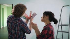 Paar die in nieuw huis de kleuren van de muurverf kiezen stock footage