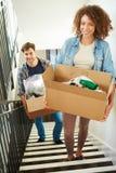Paar die in Nieuwe Huis Dragende Doos zich boven bewegen stock afbeelding