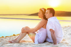 Paar die in omhelzing samen op zonsopgang letten Royalty-vrije Stock Afbeeldingen