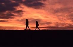 Paar die onderaan een zeer oranje zonsondergang lopen royalty-vrije stock foto