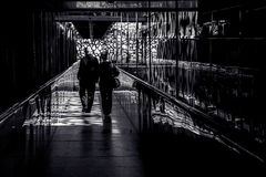 Paar die onderaan tegenover elkaar gestelde gang lopen Stock Foto's