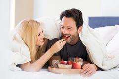Paar die ontbijt op bed eten Royalty-vrije Stock Afbeeldingen