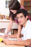Paar die op atable schrijven Stock Afbeeldingen