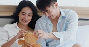 Paar die op bed liggen, zij die met teddybeer spelen stock video