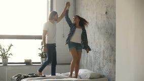 Paar die op bed, vrouw het spinnen rond de hand van holdingspartners dansen stock videobeelden