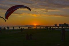 paar die op de zonsondergang op het strand letten stock afbeelding